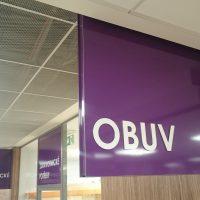 Řada fialových orientačních výstrčí a označením prodejen bílým plastickým textem, nápisy OBUV, ZDRAVOTNICKÉ POTŘEBY, PAPÍR