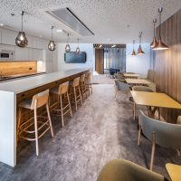 Fototapeta s motivem dřeva a povrchovou úpravou Canvas nalepená na stěně designové kuchyně, barový stůl s židlemi, dřevěné stolky s křesílky, designová stropní svítidla