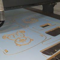 Proces gravírování a frézování dílů pro dětskou postýlku z dřevovláknité desky, stroj na desce, vyřezaný tvar medvídka a měsíčku