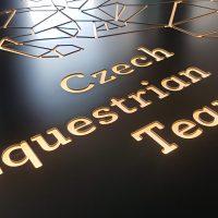 Na černé desce vyfrézovaný světlý nápis Czech Equestrian Team, každé slovo v jiném řádku, nad nápisem část geometrického loga stejné barvy
