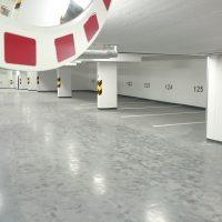 Značení uvnitř podzemního parkoviště, linky na podlaze jako vyznačení parkovacích míst, číslovky na stěně