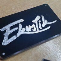 Gravírované bílé logo Ekustik na černé hliníkové destičce připevněné hřebíčky na béžovém podkladu