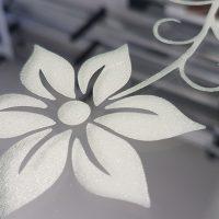 Bílá dekorativní květina gravírovaná laserem do plexiskla