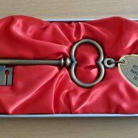 Retro historický klíč s patinací s destičkou s nípisem REKONSTRUKCE HISTORICKÉ BUDOVY NÁRODNÍHO MUZEA 20.4.2015, na červeném saténovém podkladu v krabičce na dřevěném stole