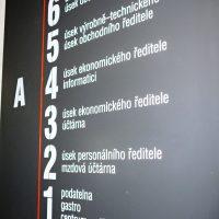 Černá hliníková informační deska s bílými značeními pater a červenou vertikální linkou, nalepená na bílé zdi