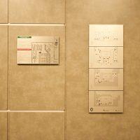 Samostatný hliníkový panel s orientačním plánem budovy, vedle čtyři panely nad sebou s označením jednotlivých pater, nalepené na zdi uvnitř O2 Universum