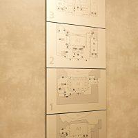 Čtyři hliníkové informační panely nad sebou, označení pater a černobílé plány podlaží, nalepené na zdi