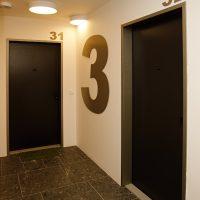 Velká hliníková číslovka 3 nalepená na zdi chodby mezi pokojovými dveřmi jako značení 3. patra, označení pokojů 31 a 32 nad dveřmi