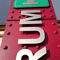 Hliníkový nápis infocentrum se zeleno-hliníkovým znakem infocentra. Vše připevněno na červený panel v exteriéru.