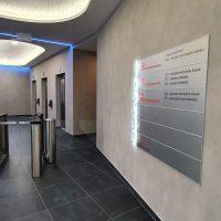 Hliníkový panel se značením budovy, svítící číslce jako označením pater, turnikety, modrá svítící lišta na stropě, chodba