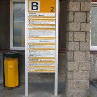 Hliníkový orientační totem označující budovu B, černé nápisy, žluté plochy, kamenný sloup, žluto-černý odpadkový koš
