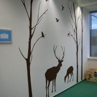 Tmavě hnědá malovaná grafika na bílé zdi, obrysy jelena, srny, stromů a ptáků, zelený koberec, část okna, knihy v knihovně