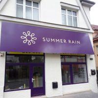 Fialová reklamní výstrč nad výlohami malého obchodu, imitace markýzy, bílé firemní logo a nápis SUMMER RAIN