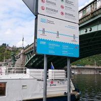 Modro-bílá informační cedule na náplavce Dvořákova nábřeží, zelený oblouk Čechova mostu, záď parníku na Vltavě