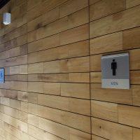 Kovová informační Dibond deska s plexisklem s piktogramem muže a nápisem MEN jako označení toalety, nalepené na dřevěné stěně, v pozadí deska s označením WC pro handicapované osoby
