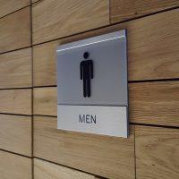 Detail kovové informační Dibond desky s plexisklem s piktogramem muže a nápisem MEN jako označení toalety, nalepené na dřevěné stěně