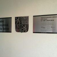 Kovová tabulka s černým nápisem Střední průmyslová škola Ostrv, vedle černobílý státní znak, vedle kovová tabulka s informačním značením, připevněno na zdi chodby