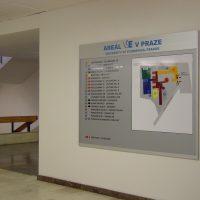 Orientační plán areálu VŠE v Praze na šedé informační tabuli, přimontováno na bílé zdi chodby, část schodiště