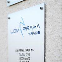Bílá informační tabulka z hliníkové desky, modré gravírované logo LOM PRAHA TRADE a černé údaje o firmě, přišroubováno na zdi