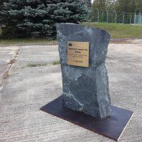 Mosazná deska ve tvaru obdélníku s černým informačním textem, přimontovaná na kamenné plastice s podstavcem, betonová dlažba, trávník, stromy