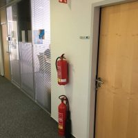 Červená informační výstrč s bílým piktogramem hasicího přístroje a požáru, připevněná na zdi chodby nad dvěma hasicími přístroji mezi dveřmi a skleněnou příčkou
