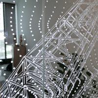Bílá inkoustová grafika s motivem teček a přímek nalepená na skleněné stěně, v pozadí interiér místnosti