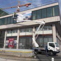 Technik na vysokozdvižné plošině instaluje potištěný banner na okna rohové budovy, v pozadí jeřáb s označením Metrostav