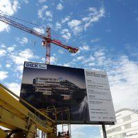 Instalace reklamního billboardu DOCK, pohled zespodu, vepředu detail vysokozdvižné plošiny, v pozadí jeřáb Metrostav