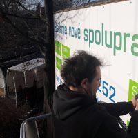 Technik na vysokozdvižné plošině vrtačkou instaluje reklamní ceduli na zeď, na zemi stojí reklamní dodávka s otevřeným kufrem