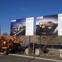 Instalace dvou reklamních billboardů před rozestavěný areál, vůz s vysokozdvižnou plošinou