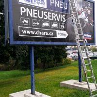 Instalace samolepicích folií na reklamní billboard, opřený žebřík, betonové podstavce na trávníku