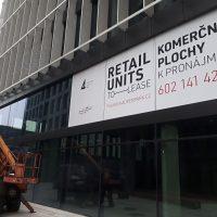 Bílé samolepicí folie s reklamními nápisy, instalované na skleněné tabule moderní budovy, vysokozdvižná plošina