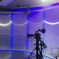 Pískovaná folie nalepená na zaoblené stěně natáčecího studia, kamera stojící na stativu, kameramanská židle, obrazovka s digitálními hodinami