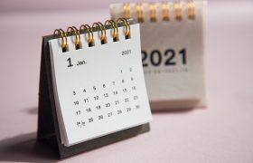 Menší stojící kalendář s bílými listy a tmavšími pevnými deskami, se zlatou kroužkovou vazbou, v pozadí další kalendář, světlý se zlatou kroužkovou vazbou, na bílém podkladu