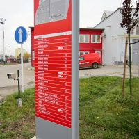 Totem s červeno-bílým orientačním plánem a popisem budov na šedé kovové základně, betonová patka na trávníku, dopravní značka