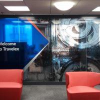 Potištěná folie na příčce v interiéru, motiv orloje, bílý nápis Welcome to Travelex na geometrickém pozadí, v popředí červená křesla