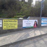 Betonová zídka podél chodníku, na ní několik reklamních cedulí z dibond desek polepených potištěnou folií, vepředu část silnice, v pozadí keře