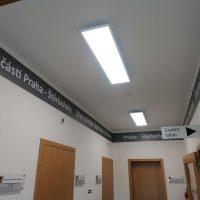 Černá informační lišta z laminované fototapety na vrchní části chodby, bílý text jako označení Úřadu Městské části Praha - Štěrboholy, dřevěné dveře, výstrč s označením směru k 2. patru a výtahu