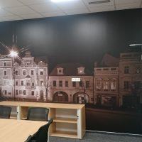 Laminovaná potištěná fototapeta s fotografií městských historických budov nalepená na zdi, dřevěná skříňka, detail dřevěného konferenčního stolu, černé židle