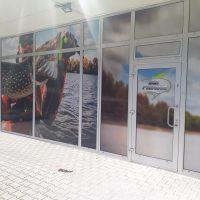 Polep výlohy AZ Fishing, potištěná folie s fotografií rybáře a ryby nalepená na skleněných tabulích mezi bílými příčkami, logo na dveřích