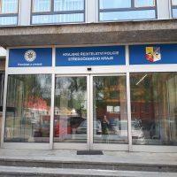 Označení budovy Krajského ředitelství policie Středočeského kraje nad skleněnými dveřmi, modře potištěná samolepicí folie s bílým textem a policejními znaky, schody před vchodem