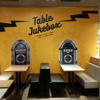 Wall wrap stěna potištěná oranžovým pozadím a černým nápisem Table Jukebox, stolky a lavice v restauraci