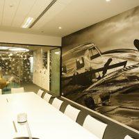 Laminovaná potištěná černobílá fototapeta s motivem starého letadla nalepená na stěně zasedací místnosti, bílý konferenční stůl a židle, sklěněná příčka polepená řezanou grafikou z pískované folie ve tvaru souhvězdí