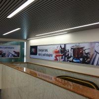 Reklamní desky v kovovém rámu, polepené barevně potištěnou folií s logem PRE a sloganem, nalepené na stěně a na skle v interiéru