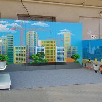 Prostorová instalace z laminovaných potištěných stěn, wall wrap s motivem městských budov, jeřábů a stavby, šedý koberec, bílé poličky