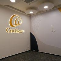 Laminová fototapeta s geometrickými tvary nalepená na stěně, svítící logo Cochlear na bílé zdi, černá podlaha, designové kruhové osvětlení