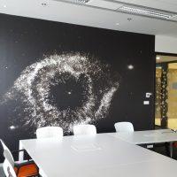 Laminovaná fototapeta s abstraktním černobílým motivem galaxie nalepená na zdi zasedací místnosti, bílý konferenční stůl, bílo-červené židle, skleněná příčka polepená pískovanou folií