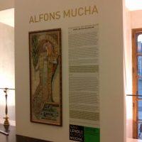 Fototapeta na bílé stěně potištěná obrazem Alfonse Muchy a doprovodným textem