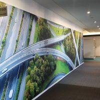 Laminovaná fototapeta s motivem silnic a automobilů nalepená na zdi chodby, výstrč s označením IT EUS, béžová podlaha, skleněné stěny místností