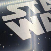 Detail bílého gravírovaného loga STAR WARS na kompozitní dibond desce v černé barvě s bílými tečkami
